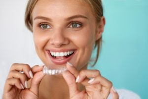 A woman holding a whitening tray.