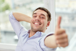 man smiling with a thumbs up