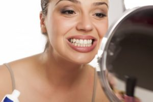 woman looking at her teeth in a mirror to find different types of tooth stains