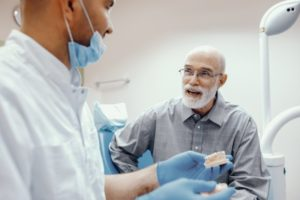senior man talking to his dentist about All-on-4 dental implants
